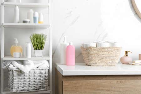 Cesta de mimbre con rollos de papel higiénico sobre encimera en el baño.