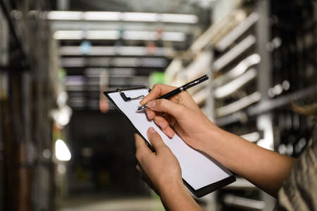 Woman with clipboard in wholesale warehouse, closeup