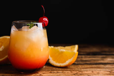 Cóctel de Tequila Sunrise con alcohol fresco en la mesa de madera