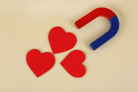 Magnet and red hearts on beige background, flat lay