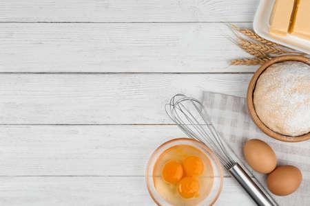 Composizione piatta con uova e altri ingredienti su tavolo di legno bianco, spazio per il testo. Torta al forno