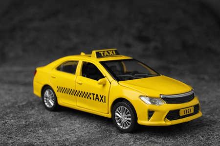 Gelbes Taxiautomodell auf grauem Hintergrund