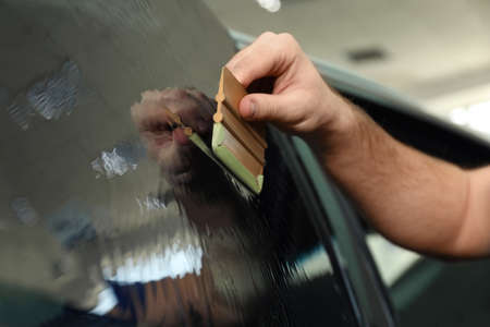 Worker tinting car window with foil in workshop, closeup
