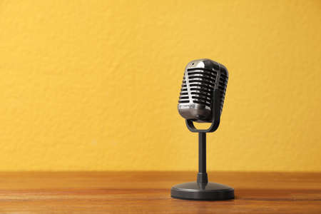 Vintage microphone on wooden table, space for text. Journalist's equipment