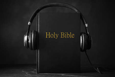 Bible and headphones on black background. Religious audiobook