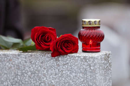 Red roses and candle on light grey tombstone outdoors. Funeral ceremony