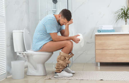 Man suffering from hemorrhoid on toilet bowl in rest room
