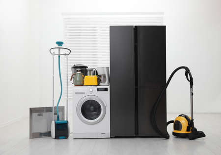 Refrigerator and different household appliances in room
