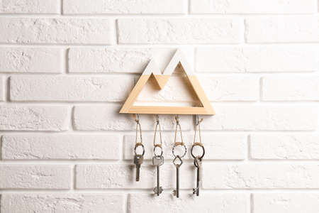 Wooden key holder on white brick wall indoors