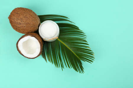 Flat lay composition with organic coconut oil on turquoise background. Healthy cooking