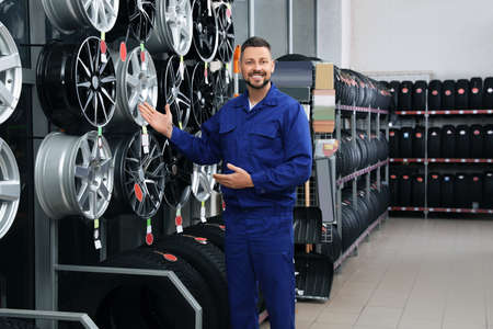 Male mechanic near car tires and alloy wheels in auto store