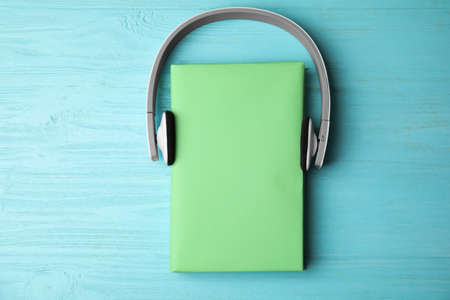 Book with blank cover and headphones on light blue wooden background, flat lay