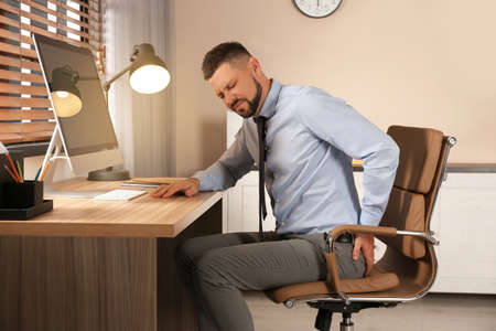 Man suffering from hemorrhoid at workplace in office