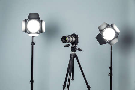 Professional video camera and lighting equipment on grey background