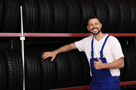 Male mechanic near rack with car tires in auto store
