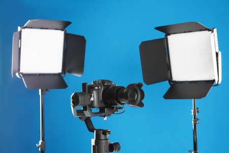 Professional video camera and lighting equipment on blue background Stock Photo