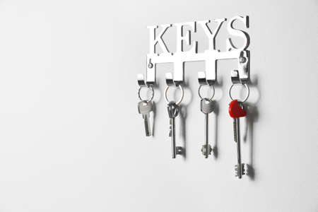 Metal key holder on light wall indoors. Space for text