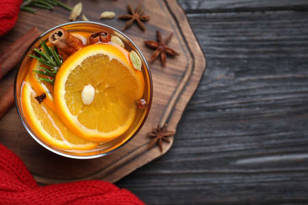 Aromatic mulled wine on black wooden table, top view. Space for text