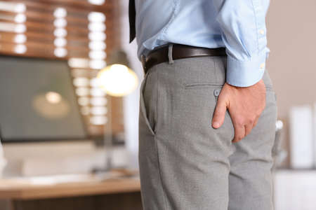 Man suffering from hemorrhoid in office, closeup