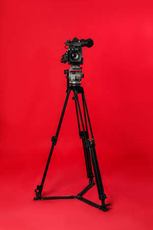 Cámara de vídeo profesional moderna sobre fondo rojo. Foto de archivo