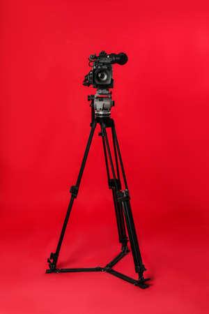 Moderne professionelle Videokamera auf rotem Hintergrund Standard-Bild