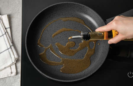Woman pouring cooking oil from bottle into frying pan, top view