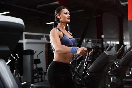 Mujer joven que trabaja en la elíptica en el gimnasio moderno