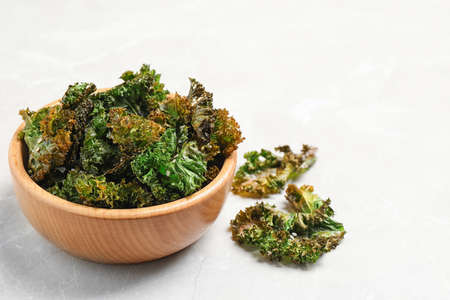 Tasty baked kale chips on grey marble table