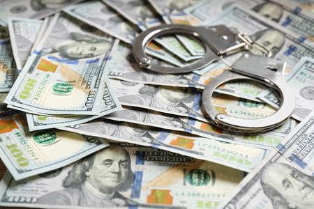 Handschellen auf Stapel von Dollarscheinen. Bestechungskonzept Standard-Bild