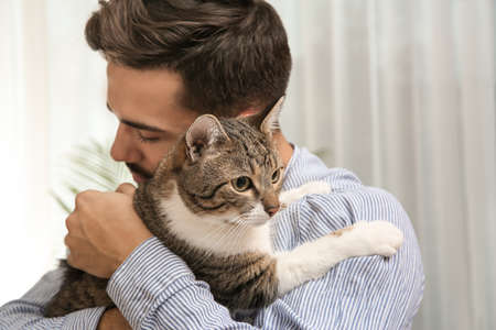 Happy man with cat at home. Friendly pet Imagens