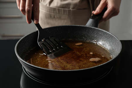 Woman holding frying pan with used cooking oil, closeup Stock fotó