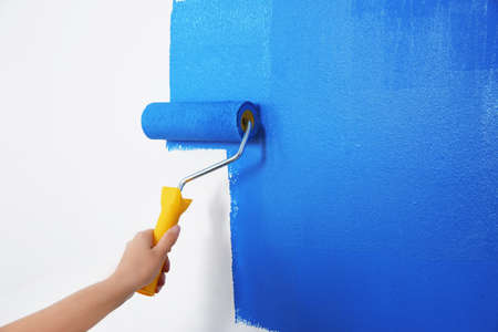 Woman painting white wall with blue dye, closeup. Interior renovation