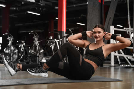 Young woman doing abdominal exercise in modern gym
