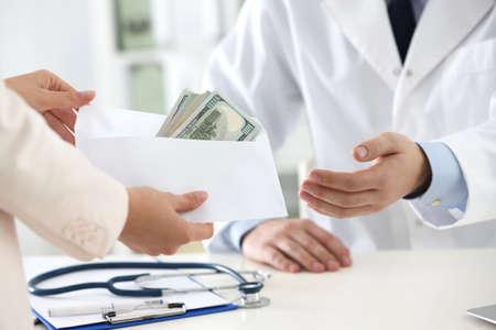 Paciente dando soborno al médico en la clínica, primer plano. Medicina corrupta Foto de archivo