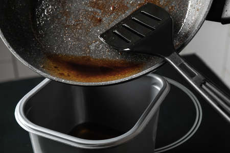Pouring used cooking oil from frying pan into container, closeup