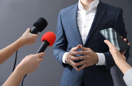 Giornalisti professionisti che intervistano uomo d'affari su sfondo grigio, primo piano Archivio Fotografico