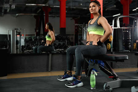 Young woman sitting on bench in modern gym