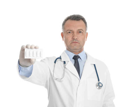 Doctor holding suppositories for hemorrhoid treatment on white background