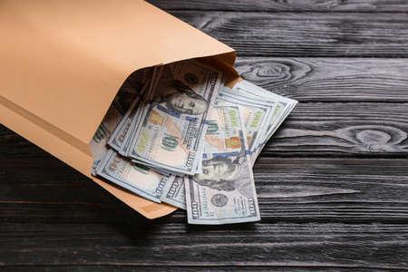 Busta con banconote da un dollaro sul tavolo di legno nero, primo piano. Corrompere il concetto