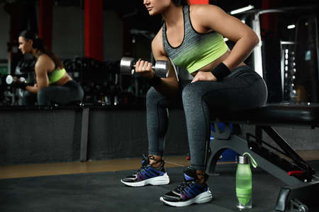 Young woman working out with dumbbell in modern gym, closeup