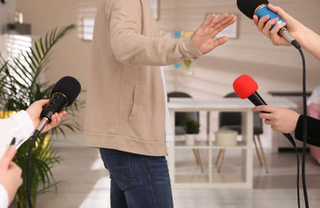 Man avoiding journalist's questions at interview indoors, closeup view