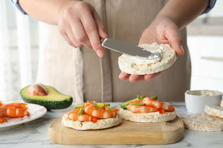 Woman spreading butter on puffed rice cake over white table indoors, closeup Banco de Imagens