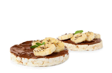 Puffed rice cakes with chocolate spread, banana and mint isolated on white Banco de Imagens