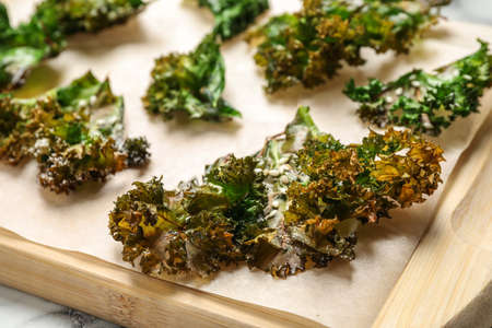 Tasty baked kale chips on wooden board, closeup