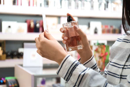 Young woman spraying perfume on blotter in shop, closeup