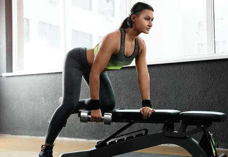 Young woman working out with dumbbell in modern gym