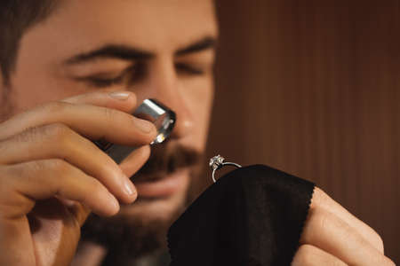 Jeweler working with ring on blurred background, closeup