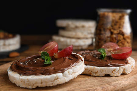 Puffed rice cakes with chocolate spread and grape on wooden board, closeup