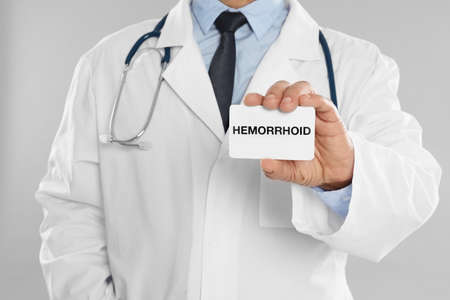 Doctor holding business card with word HEMORRHOID on light grey background, closeup
