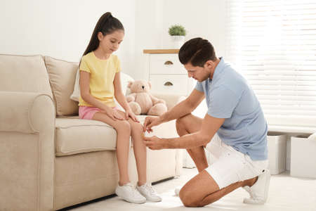 Father putting sticking plaster onto daughters leg at home Stok Fotoğraf